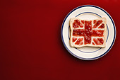 A slice of bread with a union jack flag of strawberry jam - Stock Image - C5NDGA