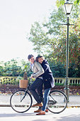 Couple riding bicycle in park - Stock Image - CC9FK1