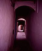 Pink street through archway medina Essaouira Morocco - Stock Image - ADMHA0