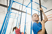 Boy climbing rope in gym - Stock Image - DN94WA