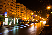 Larnaka Finikoudes promenade at night with light trails from passing cars - Stock Image - E46DAT