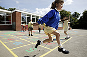 Schoolgirls skipping in a primary school playground in the UK. - Stock Image - BDP7AN