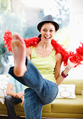 Woman dancing in hat and feather boa - Stock Image - BN2H65