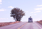 Airstream trailer on open country road - Stock Image - AD7AFD
