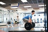 Man doing deadlifts in fitness center - Stock Image - DA725T