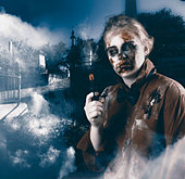 Cruel monster in foggy cemetery late at night holding gun. Grave robber - Stock Image - DTKN64