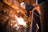 Worker cleaning mould in metal foundry - Stock Image - D556GY