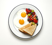 A breakfast serving of fried eggs, toast and mixed fruits - Stock Image - B7CBCB