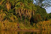 Buhsman in dugout canoe, Okavango Delta, Botswana - Stock Image - BF8R5H