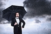 Unhappy Man Holding Umbrella in a Rain Storm and Frowning - Stock Image - CT3Y6R
