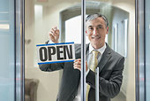 Chinese businessman hanging Open sign in window - Stock Image - DYNDR2