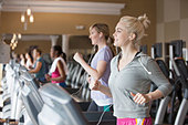 Caucasian women exercising on treadmills in gym - Stock Image - DTY6BF
