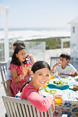 Family eating lunch at table on sunny patio overlooking ocean - Stock Image - DRCKD3