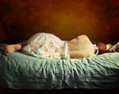 Young woman sleeping in red room with bare back on green sheets - Stock Image - CETN84