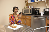 Mixed race businesswoman eating lunch in break room - Stock Image - BK0PEX
