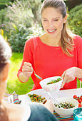 Woman Having Lunch in Garden with Friend - Stock Image - DTA0XJ