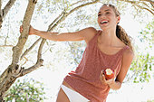 Smiling woman eating apple outdoors - Stock Image - D5WR9R