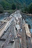 Suspension bridge over a river in the mountains of Abkhazia - Stock Image - E49B4T