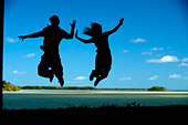 A couple leap into the air in Everglades National Park, Florida. (silhouette) - Stock Image - BFDCXY