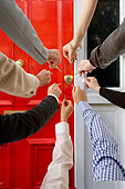 Several hands trying to open a front door - Stock Image - B1DCP0
