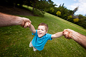 Father Spinning Son Outdoors in Park - Stock Image - D68KG4