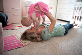 Mom holding her eleven month old girl up and playing in bedroom. - Stock Image - CRW3T4