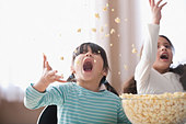 Playful girls throwing popcorn - Stock Image - CBT654