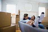 Affectionate homosexual couple relaxing sofa among moving boxes - Stock Image - ERBP7H