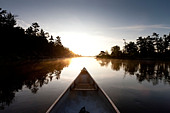 Bow of a canoe on the French River at dawn in French River Provincial Park, Ontario, Canada - Stock Image - CFD112