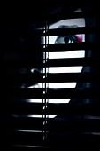 A partially hidden face of a young woman behind a screen - Stock Image - BDPMR1