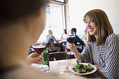 Women enjoying lunch and wine at bistro - Stock Image - E3R5M7