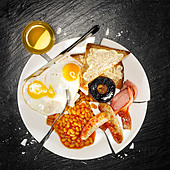 A full breakfast containing bacon, eggs, sausage, baked beans, mushroom and toast - Stock Image - BEJXJF