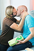 Two gay men making out in the kitchen - Stock Image - BKWE57