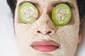 Close-up of a man with facial mask and cucumber slices on eyes - Stock Image - D0W3EJ