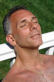 Closeup Portrait of a Man Soaking in the Sun He is Leaning Against a White Rail - Stock Image - B4BE1R