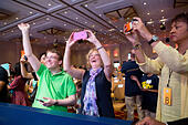 """National Harbor, USA. 27th May, 2015. Deb Gribben, center, of Glen Allen, Virginia, cheers for her former student, Tejas Muthusamy, 12, now a sixth grader at George Moody Middle School in Richmond, Virginia, during a break in round two - one of the preliminary rounds - of the 2015 Scripps National Spelling Bee being held at the Gaylord National Resort and Conference Center on May 27, 2015 in National Harbor, Md. Muthusamy's parents paid for Gribben to come to the event. """"I'm so excited for him,"""" she exclaimed as she took his photo. © Allison Shelley/McClatchy DC/TNS/Alamy Live News - Stock Image - ER6N7G"""