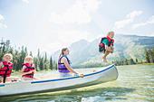 Caucasian boy jumping from canoe into lake - Stock Image - DJAE4H