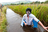 Llanwrtyd Wells, UK. 30th August, 2015. Steve Meadows from Leicester dresses up as Elvis Presley for the Bog Snorkelling. World Bogsnorkelling Championships were conceived 30 years ago in a Welsh pub by landlord Gordon Green, and are held every August Bank Holiday at Waen Rhydd Bog. Using unconventional swimming strokes, participants swim two lengths of a 55 metre trench cut through a peat bog wearing snorkel and flippers. The world record was broken in 2014 by 33 year old Kirsty Johnson from Lightwater, Surrey, in a time of 1 min 22.56 secs. © Graham M. Lawrence/Alamy Live News - Stock Image - F1919M