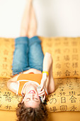 Woman talking on cell phone while laying upside down - Stock Image - AAMW93