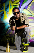 young afro-american man sitting in front of colorful graffiti wall - Stock Image - CC74FP