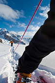 Low angle view of roped skiers leaving the camp on the Triumvirate Glacier  to climb Mount Torbert, Tordrillo Mountains, Alaska - Stock Image - C91MXD