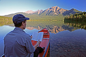 Middle age male reading book in canoe on mountain lake. - Stock Image - BFHK50