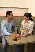 young woman and her gay friend sharing a smile in cafe - Stock Image - A3KYRB