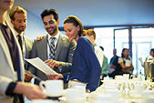 Portrait of businesspeople in lobby of conference center during coffee break - Stock Image - ECX6B8