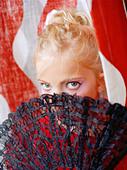 Flamenco-girl hiding behind a fan - Stock Image - A1J3RA