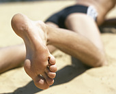 Young man lying on a beach, close-up of a bare foot - Stock Image - ADE049