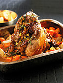Stuffed lamb shank with vegetables & rosemary in roasting dish - Stock Image - BJPHH8