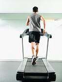 Mixed race man running on treadmill - Stock Image - CMRKR9