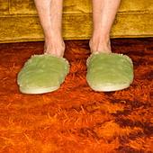 Caucasian senior female feet wearing green bedroom slippers on carpet - Stock Image - A8JD1G