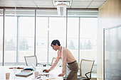 Doctor working at laptop in hospital conference room - Stock Image - EJRTM2
